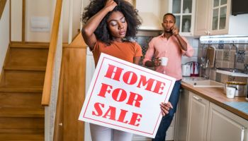 African couple having problems, woman holding a sign for sale