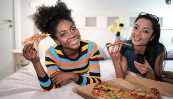 Girlfriends eating pizza in bed and watching TV stock photo