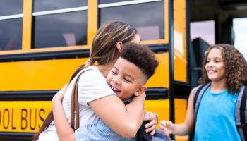 Unrecognizable mid adult mom gives children hugs before school