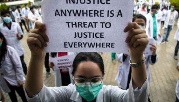 A doctor wearing a facemask holds out a protest placard...