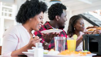 Latin family consisting of Latino man with brown skin and afro hair and two Latin women with brown skin and afro hair, one of them 52 and the other 29 are all sitting in a beautiful restaurant with typical Colombian food