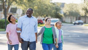 Interracial family, two children, taking walk together