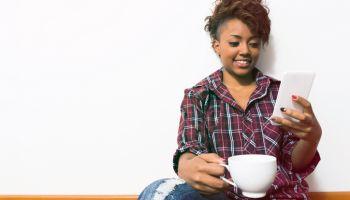 Black young woman sitting down on floor checking her social media enjoying coffee