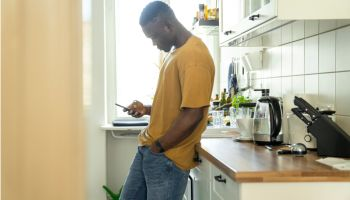 Man using smart phone in kitchen at home