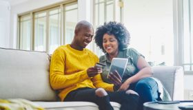 Smiling couple sitting on their living room sofa and using a tablet